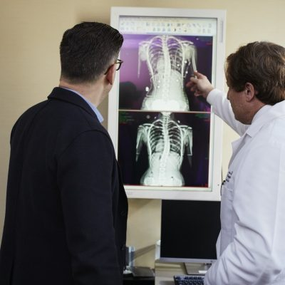 doctor-pointing-x-ray-result-beside-man-wearing-black-suit-2182972